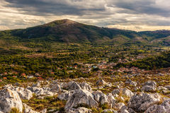 Houses in the valley. A beautiful mountain landscape with a vibrant, dramatic sky and some clouds Royalty Free Stock Photography