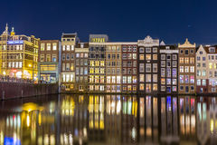 Houses on the Warmou straat reflected in the water of Damrak Royalty Free Stock Image