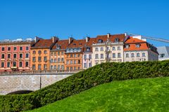 Houses of Warsaw. Hedge with lawn and row of historic tenement houses in city of Warsaw in Poland stock image
