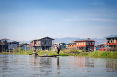 Houses on wood piles and burmese people in a boat in a village at Inle Lake, Burma Myanmar royalty free stock photos