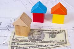 Houses of wooden blocks and currencies dollar on construction drawing, building house concept Stock Photos