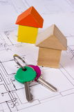 Houses of wooden blocks and keys on construction drawing of house, building house concept Royalty Free Stock Photo