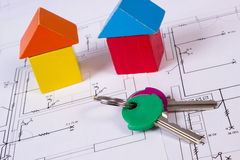 Houses of wooden blocks and keys on construction drawing of house, building house concept Royalty Free Stock Photography