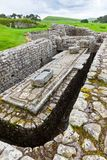 Housesteads Roman Fort. NORTHUMBERLAND, ENGLAND - JULY 7, 2012: The remains of the latrines at Housesteads Roman Fort, a part of Hadrian`s Wall in Northumberland Royalty Free Stock Photography