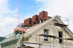 Housetop of new building will be roofed. The roof of a detached house is tiled with bricks Royalty Free Stock Photography