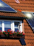 Housetop with solar. An flowers on the window Royalty Free Stock Photos