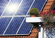 Housetop with solar. An flowers on the window Royalty Free Stock Images