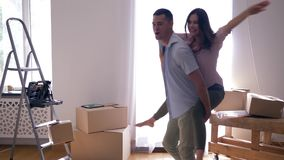 Housewarming, happy Lovers is having fun and boyfriend is Carrying girl on back among boxes during moving to apartment