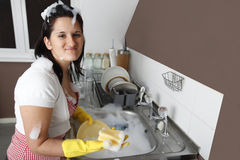 Housewife. A stereotypical housewife expressing her disappointment at having to do all the house chores. She is in a real mess after washing the dishes Royalty Free Stock Photography