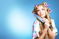 Housewife. Portrait of a pretty girl with curlers in her hair holding a knife. Over grey background stock photo
