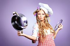Housewife. Beautiful blonde woman housewife holding pan. Studio shot over grey background Stock Photography