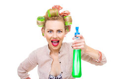 Housewife. Surprised housewife / woman spraying the cleaner on you, isolated on white. Glass or window cleaner royalty free stock image