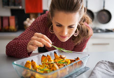 Housewife adding rosmarinus to baked pumpkin Royalty Free Stock Image