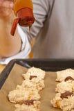 Housewife applying chocolate icing Stock Image