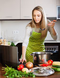 Housewife in apron cooking with laptop Stock Image
