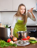 Housewife in apron cooking soup with notebook Royalty Free Stock Image