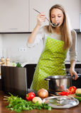 Housewife in apron cooking soup with notebook Royalty Free Stock Images