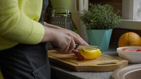 Housewife in apron cuts yellow sweet pepper paprika with knife on wooden board