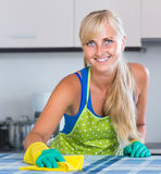 Housewife in apron with rag and cleanser cleaning up royalty free stock images