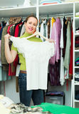 Housewife arranging clothes at wardrobe Stock Photos