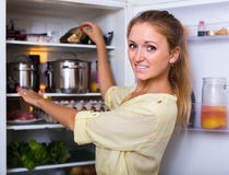 Housewife arranging food on fridge shelves Stock Image