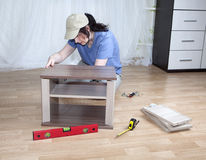 Housewife assembles nightstand in the interior of his apartment. Royalty Free Stock Photography