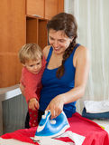 Housewife with baby  ironing clothes Stock Image