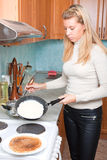 Housewife bakes pancakes. Young housewife bakes pancakes, kitchen Stock Images