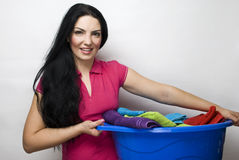 Housewife with basket of clean laundry. Smiling beauty housewife holding a blue basket with clean laundry royalty free stock images