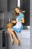 Housewife with basket in the kitchen Stock Photo