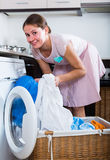 Housewife with basket of linen near washing machine indoors Stock Image