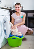 Housewife with basket of linen near washing machine indoors Stock Photos