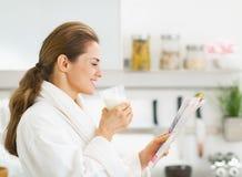 Housewife in bathrobe drinking milk and reading magazine Stock Photos