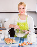 Housewife beating eggs and milk in bowl Royalty Free Stock Photography