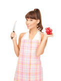 Housewife with big knife and radish Royalty Free Stock Photography
