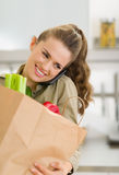 Housewife with big shopping bag talking cell phone Stock Photo