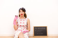Housewife with black chalkboard with a to do list and glass of wine in hand Royalty Free Stock Photo