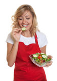 Housewife with blonde hair tasting her salad Royalty Free Stock Photography