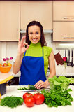 Housewife in blue apron showing ok sign Royalty Free Stock Photography