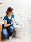 Housewife in blue cleaning toilet bowl Royalty Free Stock Photography