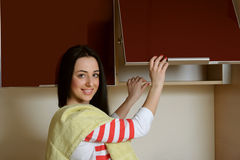 Housewife brunette in home clothes kitchen cupboard opens Royalty Free Stock Photo