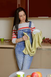 Housewife brunette in home clothes wipes saucer. Stock Images