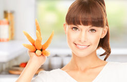 Housewife with carrots at the kitchen Royalty Free Stock Photography