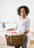Housewife carrying laundry basket Stock Image
