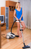 Housewife in casual hoovering at home Royalty Free Stock Photography