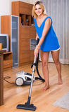 Housewife in casual hoovering at home Stock Images