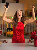 Housewife with cell phone rejoicing Royalty Free Stock Photo
