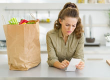 Housewife checking bill after shopping in kitchen Royalty Free Stock Photography