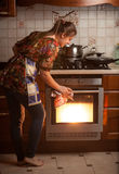 Housewife checking dish cooking in oven Stock Photo