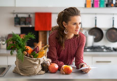 Housewife with checks after grocery shopping. Portrait of young housewife with checks after grocery shopping Stock Photo